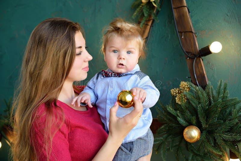 愉快的家庭母亲和使用在家圣诞节假日,新年` s的婴孩小儿子画象  免版税图库摄影