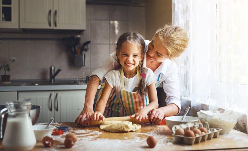 愉快的家庭母亲和女儿在厨房里烘烤揉的面团 免版税库存照片