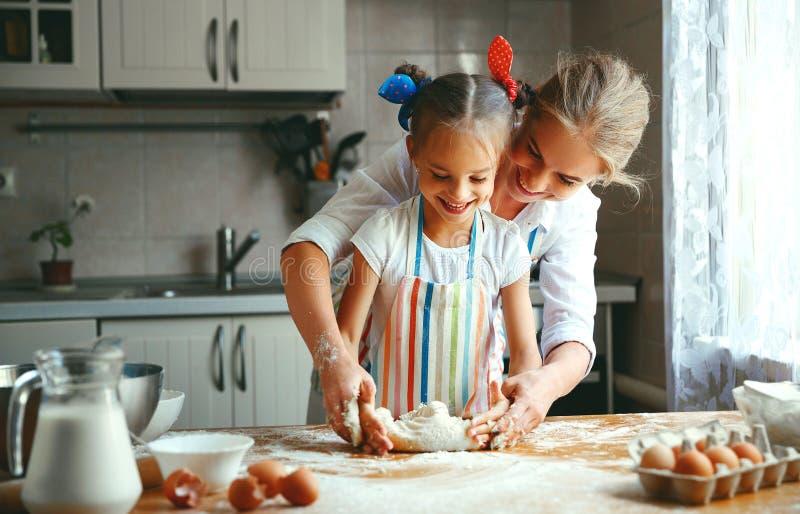 愉快的家庭母亲和女儿在厨房里烘烤揉的面团 免版税图库摄影