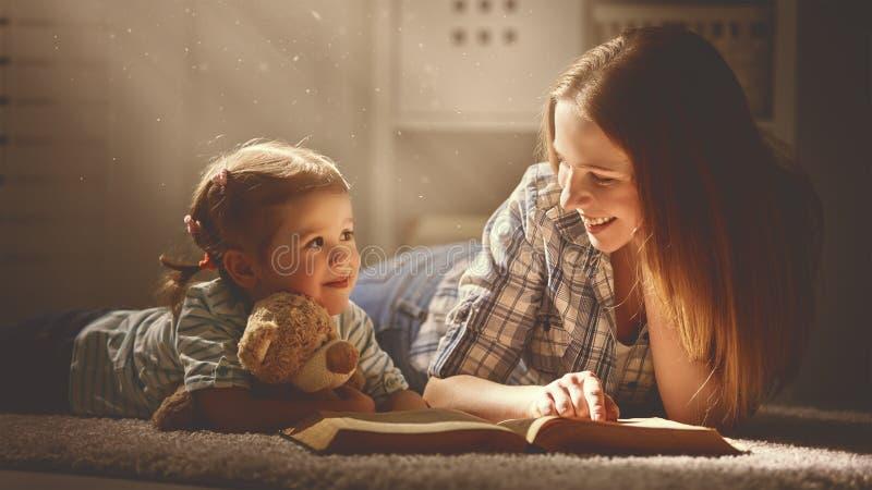 愉快的家庭母亲和女儿在晚上读了一本书 库存照片