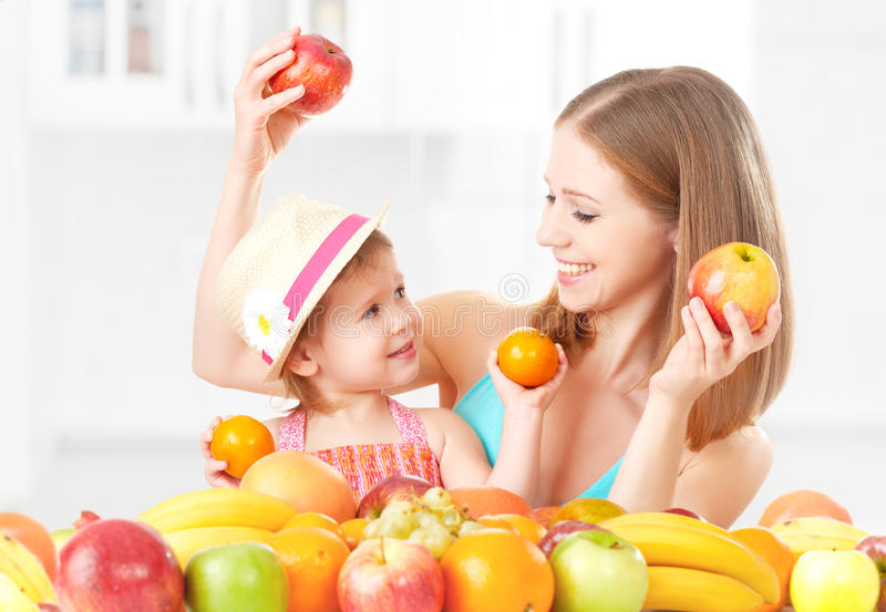 愉快的家庭母亲和女儿小女孩,吃健康素食食物,果子 免版税库存照片