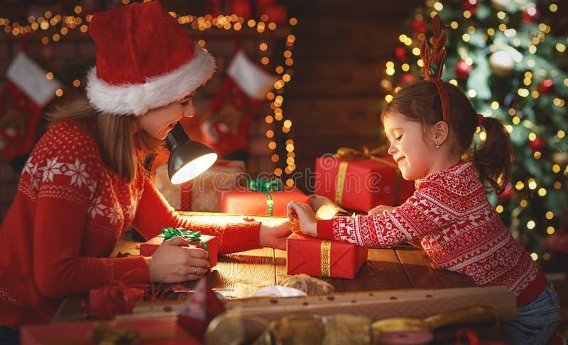 愉快的家庭母亲和孩子包装圣诞节礼物 免版税库存图片