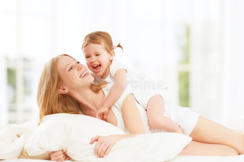 愉快的家庭母亲和小女儿使用的和笑的婴孩 图库摄影