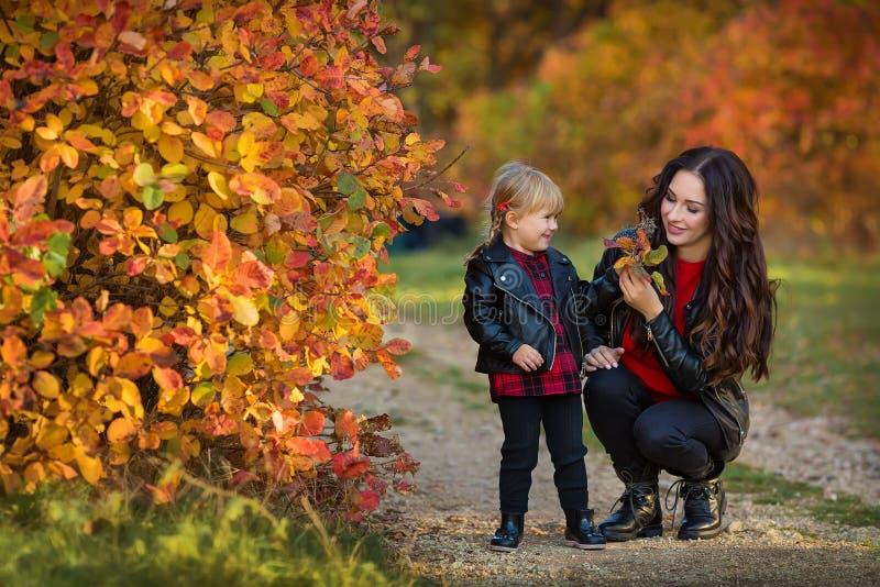 愉快的家庭母亲和跑和使用在秋天步行的儿童小女儿 库存照片