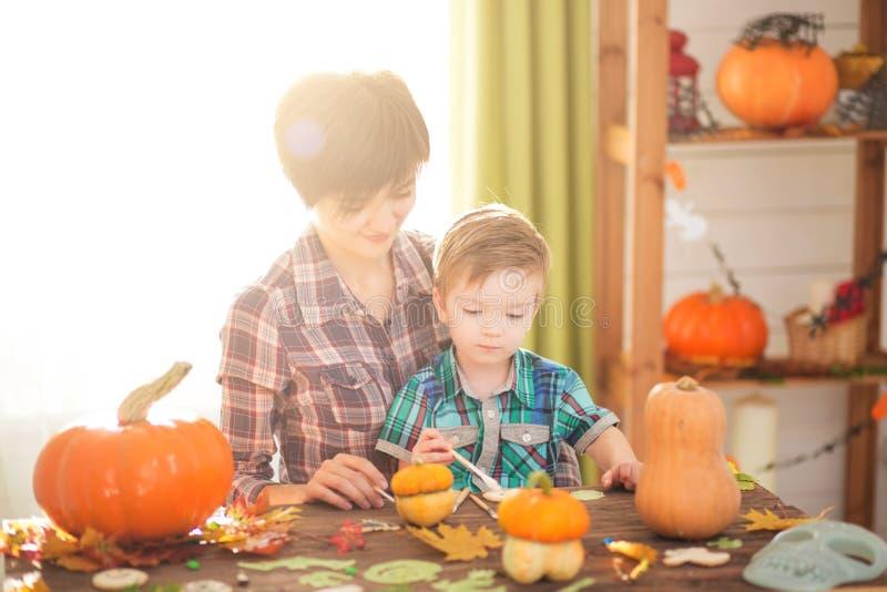 愉快的家庭母亲和雕刻南瓜的儿童儿子 愉快的家庭为万圣夜做准备 图库摄影