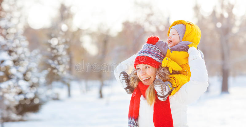 愉快的家庭母亲和婴孩是在冬天步行的愉快的雪 免版税图库摄影