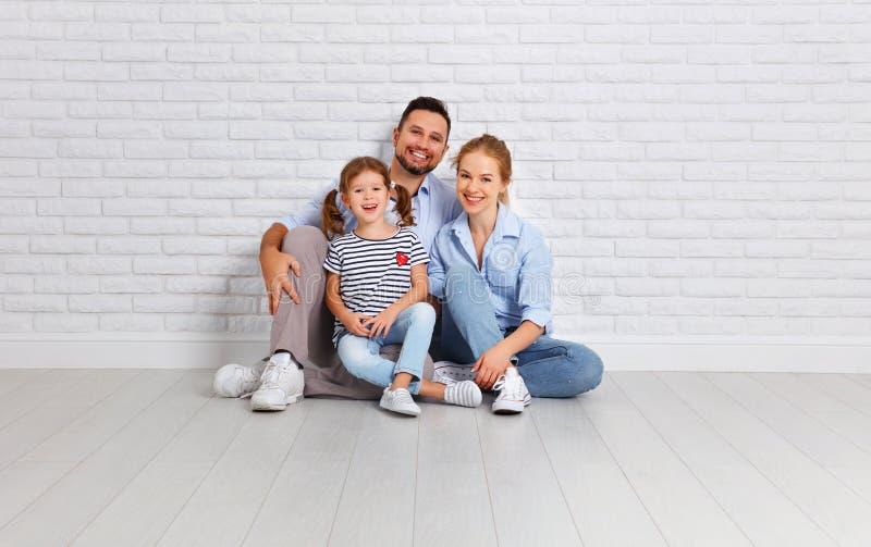 愉快的家庭母亲父亲和孩子在一个空的砖墙附近 库存图片