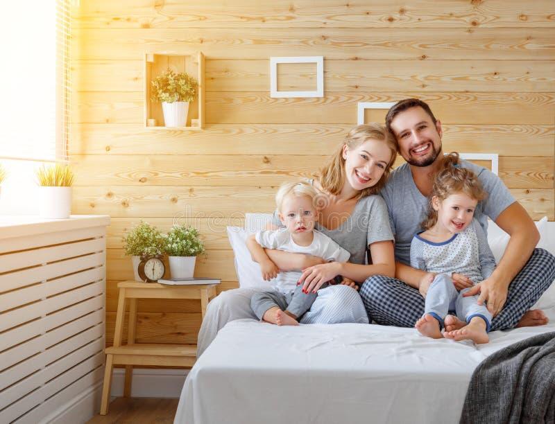 愉快的家庭母亲父亲和孩子女儿和儿子在床上 免版税库存图片