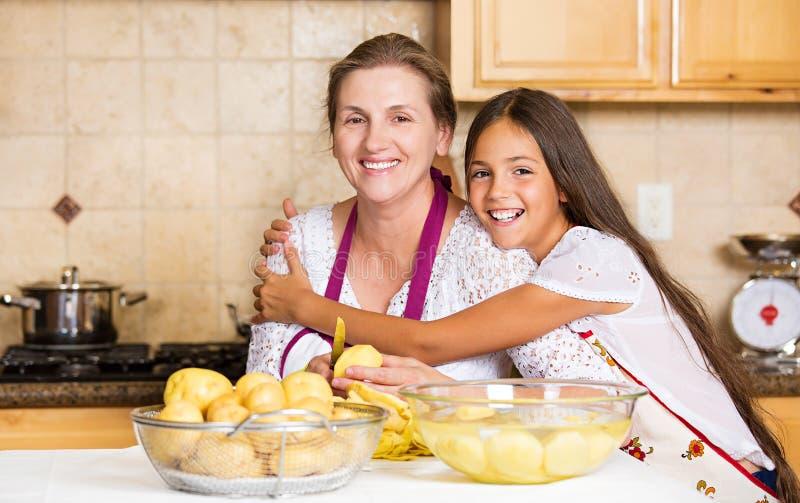 愉快的家庭母亲,烹调在厨房的女儿食物 库存图片