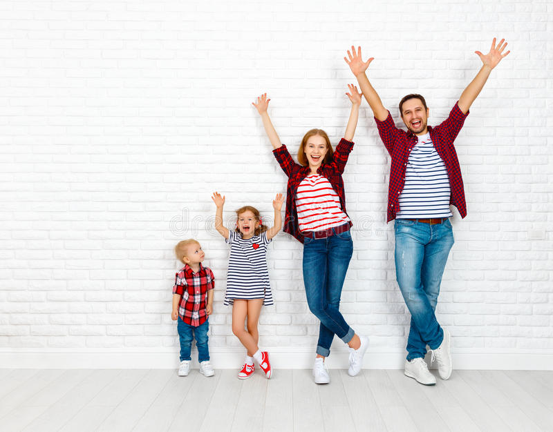 愉快的家庭母亲,父亲,儿子,在白色死墙上的女儿 库存照片