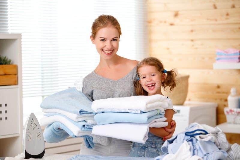 愉快的家庭母亲主妇和儿童女儿电烙的衣裳 免版税库存图片