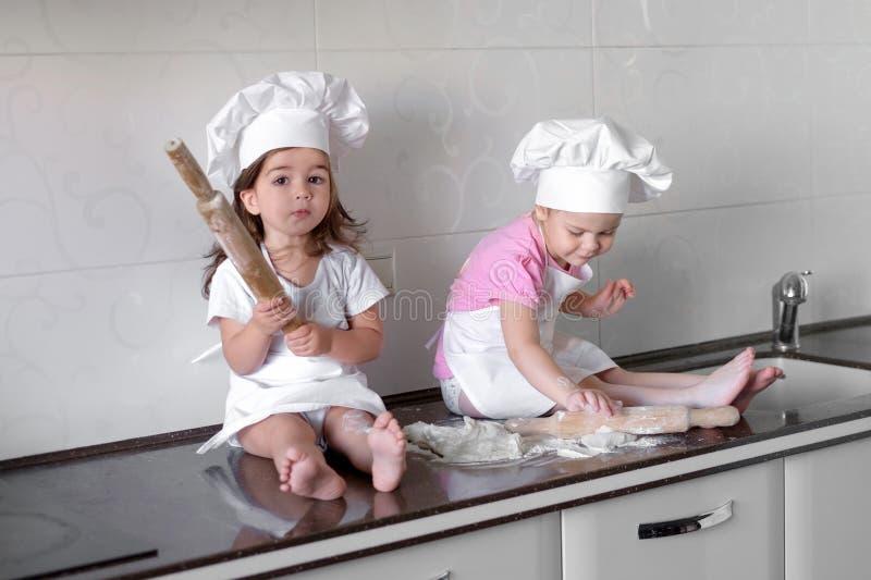 愉快的家庭滑稽的孩子在厨房里准备面团,烘烤曲奇饼 免版税库存照片