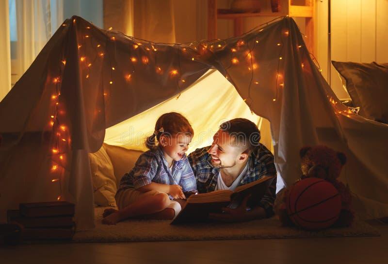 愉快的家庭父亲和读在帐篷的儿童女儿一本书 图库摄影