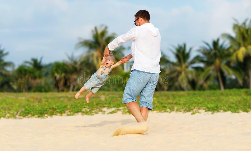 愉快的家庭父亲转动海滩的小儿子 免版税图库摄影