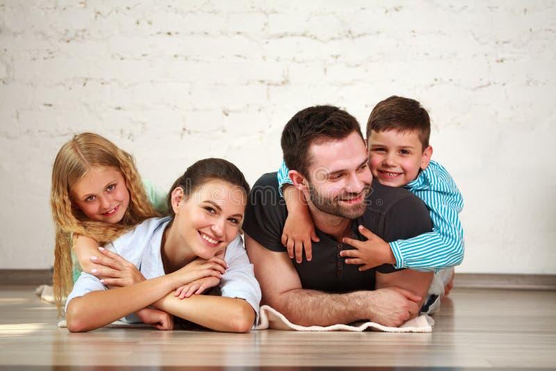 年轻愉快的家庭父母和两个孩子回家演播室 免版税库存照片