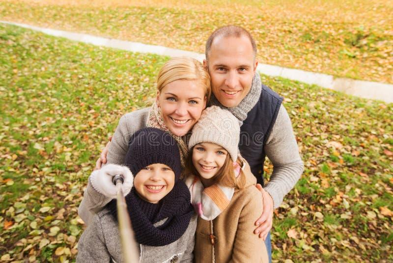 愉快的家庭用selfie棍子在秋天公园 免版税库存照片