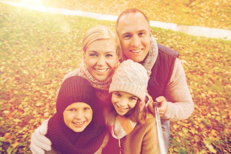 愉快的家庭用selfie棍子在秋天公园 库存图片