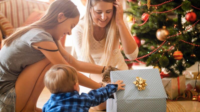 愉快的家庭画象从圣诞老人接受了在圣诞节礼物盒的小猫 免版税库存照片