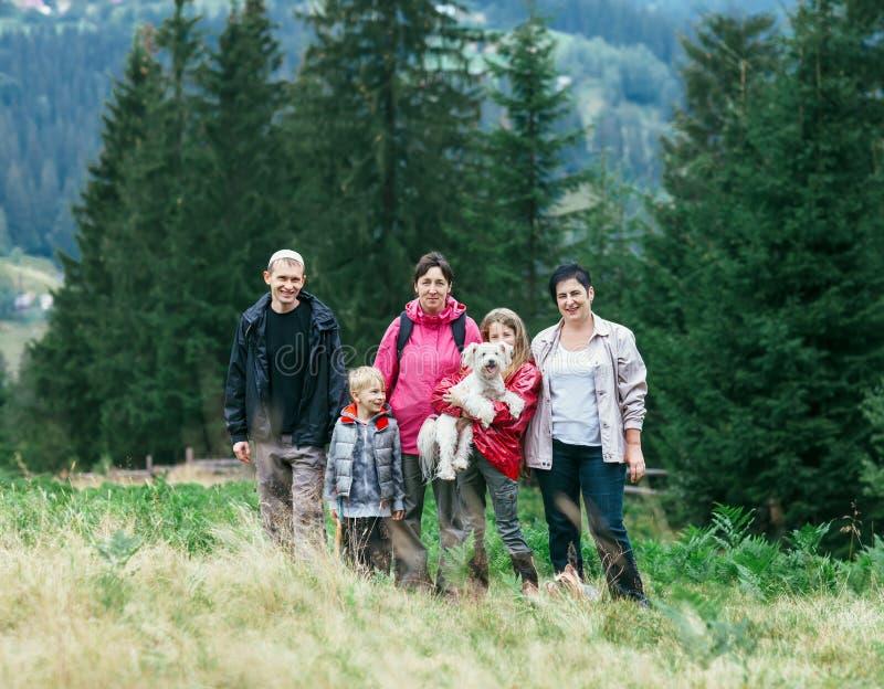 愉快的家庭画象反对树背景的户外 库存照片