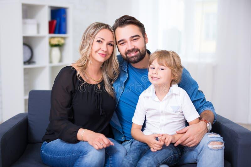愉快的家庭画象-夫妇和小儿子坐沙发 免版税图库摄影