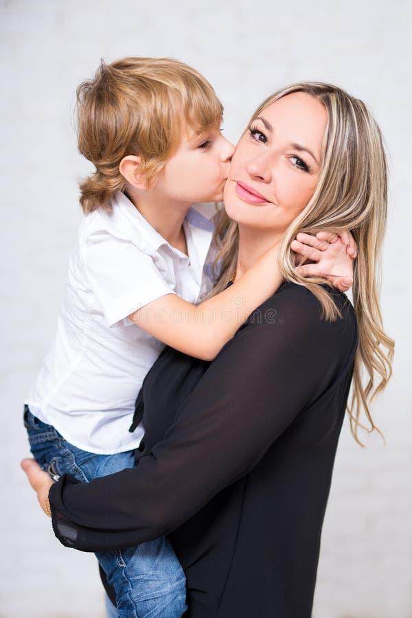 愉快的家庭画象-摆在w的母亲和逗人喜爱的矮小的儿子 库存图片