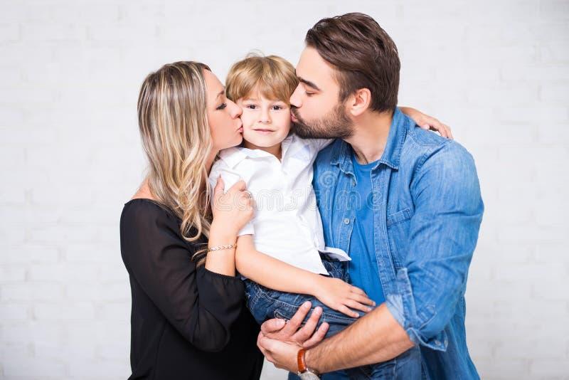 愉快的家庭画象-结合亲吻在白色的小儿子 免版税库存图片
