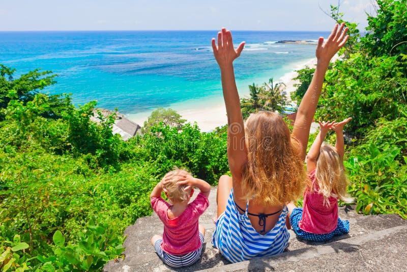 愉快的家庭看看在白色沙子海滩的海海浪 免版税库存图片