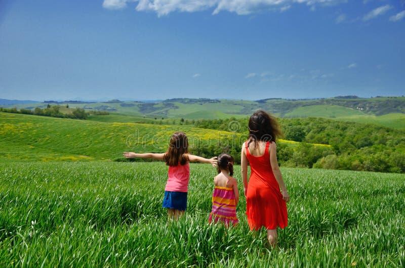 愉快的家庭获得乐趣户外在绿色领域、母亲和孩子春假在托斯卡纳,意大利 免版税库存照片