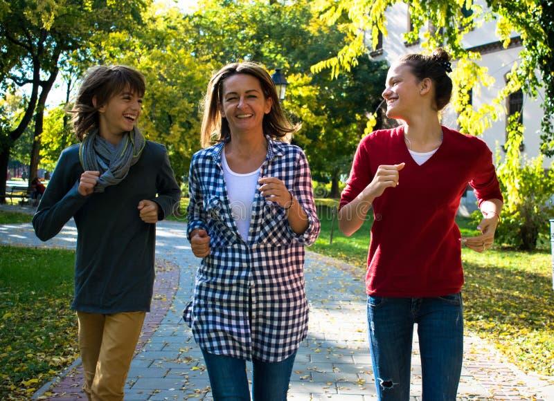 愉快的家庭获得乐趣,当跑在公园时 免版税库存图片