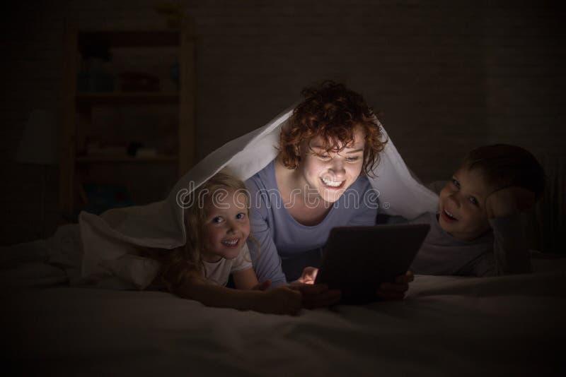 愉快的家庭读书在晚上 库存照片