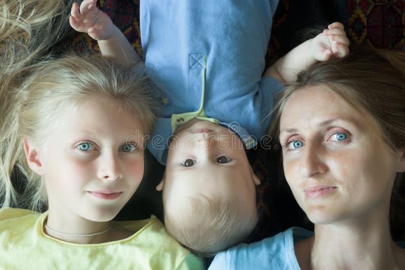 愉快的家庭顶上的射击与母亲和两可爱的兄弟姐妹的 免版税库存照片