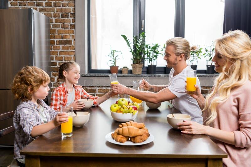 愉快的家庭饮用的汁液和吃早餐侧视图  免版税库存照片