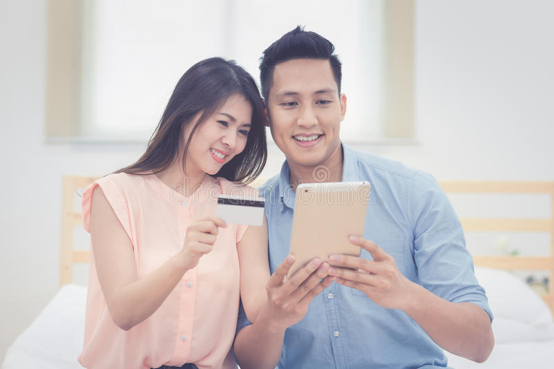 愉快的家庭,亚裔夫妇恋人喜欢使用巧妙的片剂 图库摄影
