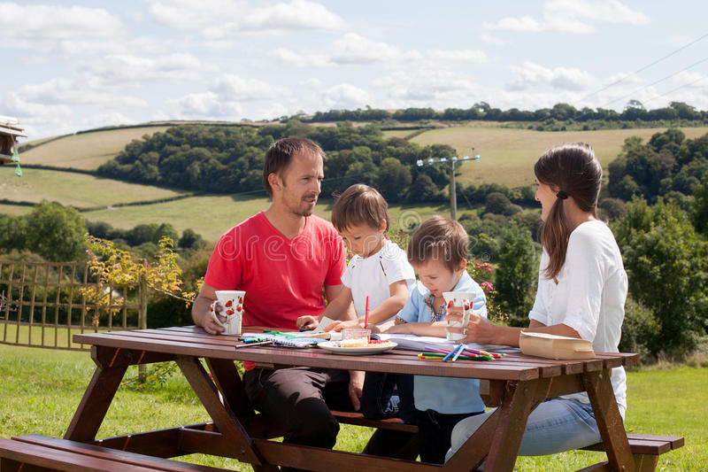 愉快的家庭,坐长凳室外,饮用的咖啡和ta 免版税库存图片