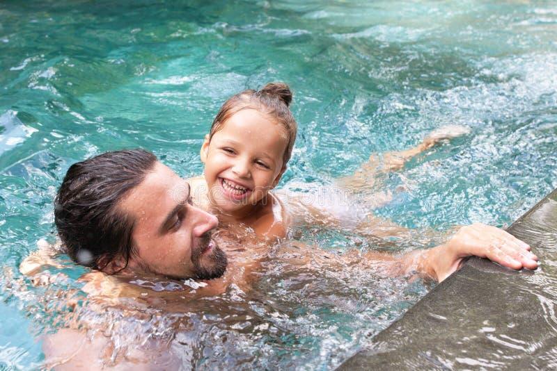 愉快的家庭,有小孩的活跃父亲,可爱的小孩女儿,获得乐趣在游泳池 免版税库存图片