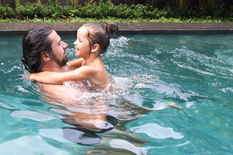 愉快的家庭,有小孩的活跃父亲,可爱的小孩女儿,获得乐趣在游泳池 库存图片