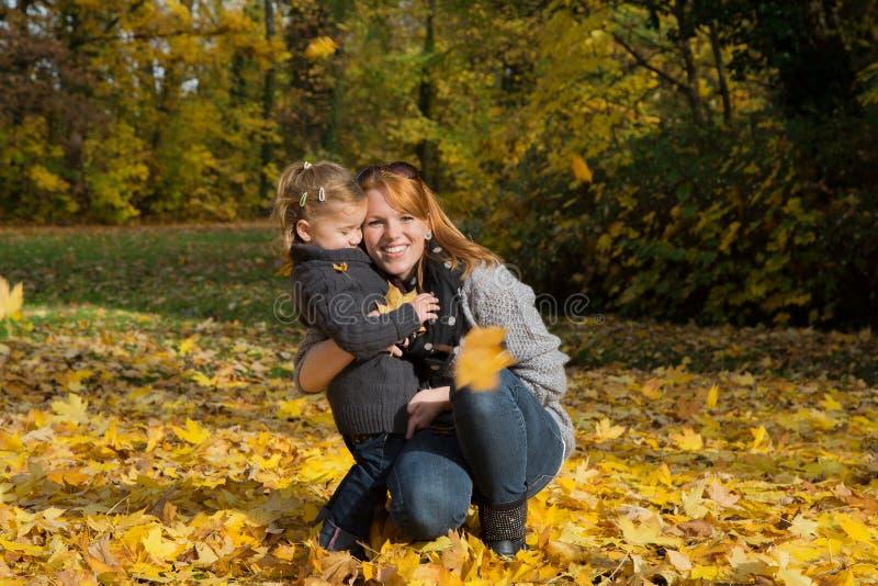 愉快的家庭:有她的做在a的小女儿的母亲步行 免版税库存图片