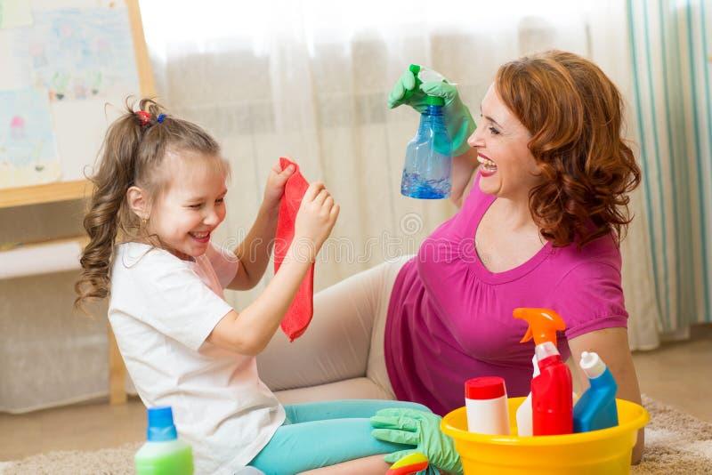 愉快的家庭-妇女和她逗人喜爱的矮小的女儿获得乐趣,使用喷雾器和旧布,当清洗他们的房子时 免版税库存图片