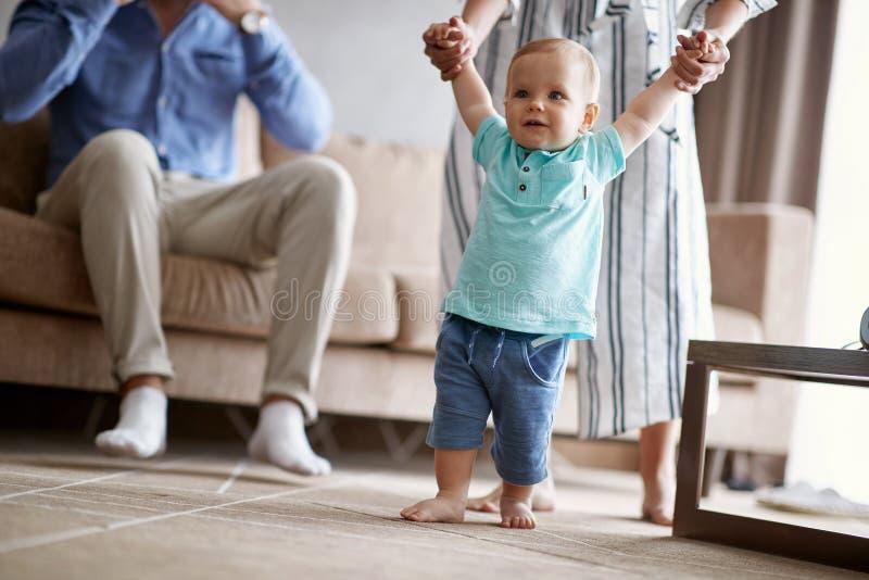 愉快的家庭-学会走与母亲,孩子e的微笑的婴孩 库存照片