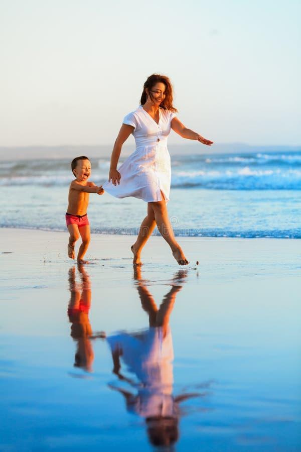愉快的家庭-母亲,婴孩在日落海滩跑 免版税图库摄影