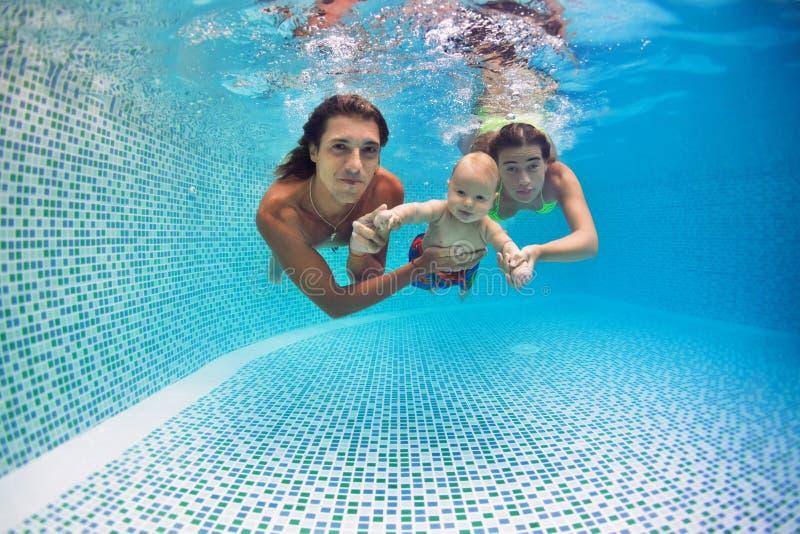 愉快的家庭-母亲,父亲,儿子下潜水下在游泳池 免版税库存图片