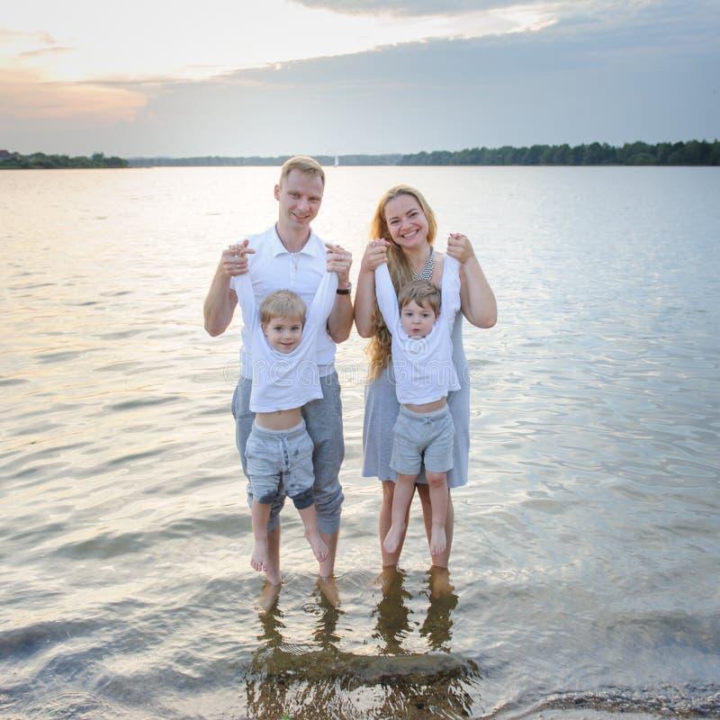 愉快的家庭-父亲,母亲,海滩的两个儿子与他们的脚在水中在日落 免版税库存照片