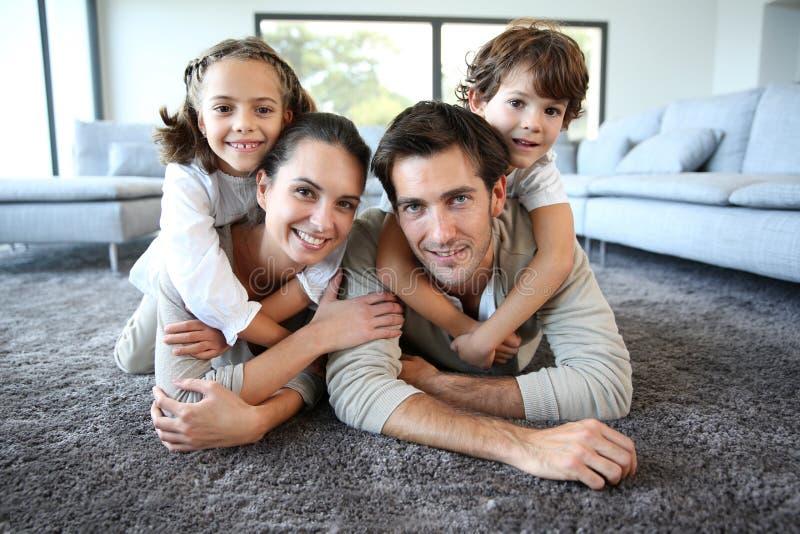 年轻愉快的家庭画象在地毯地板上的 免版税图库摄影