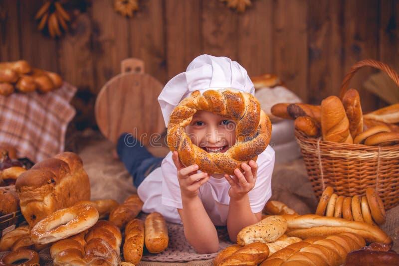 愉快的小厨师是佩带很多小圆面包的贝克 免版税库存图片