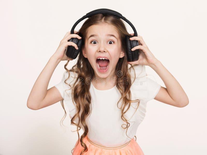 愉快的小女孩听到在耳机的音乐,白色背景 免版税库存图片
