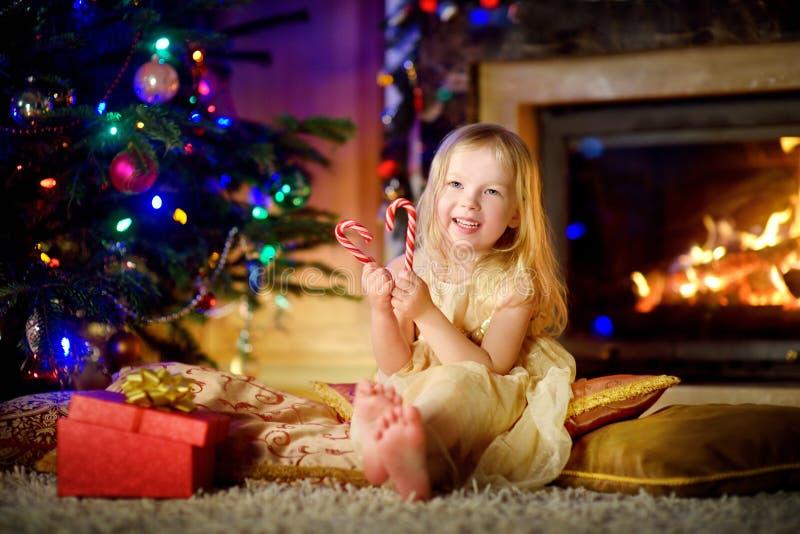 愉快的小女孩圣诞节画象由一个壁炉的在一个舒适黑暗的客厅 免版税库存图片