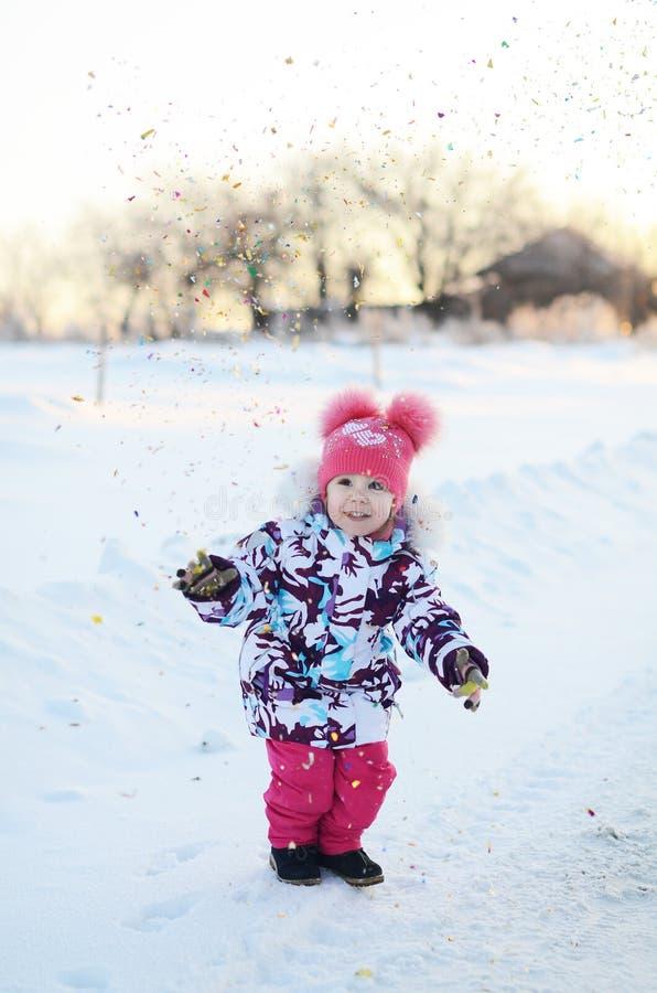 愉快的小女孩在五彩纸屑阵雨跳 免版税库存照片