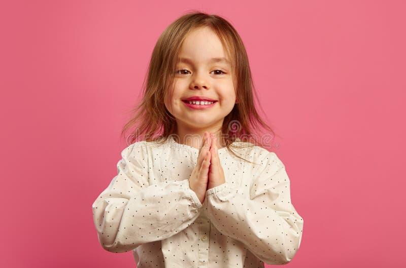 愉快的小女孩在棕榈手上折叠了她的手在胸口前面,恳切地相信履行对梦想,做愿望 库存照片