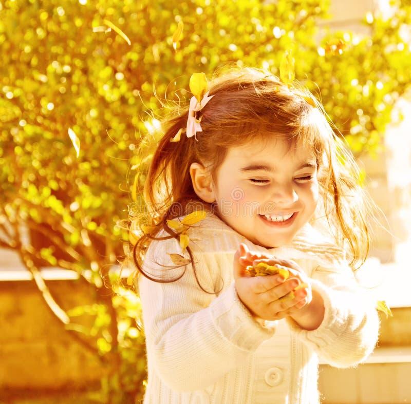 愉快的小女孩在秋天公园 免版税库存图片