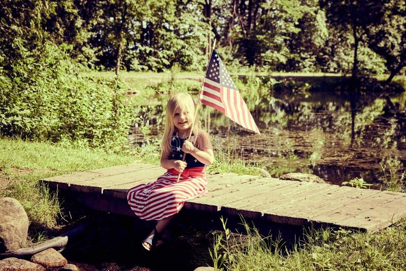 愉快的小女孩坐有美国旗子的桥梁 库存图片